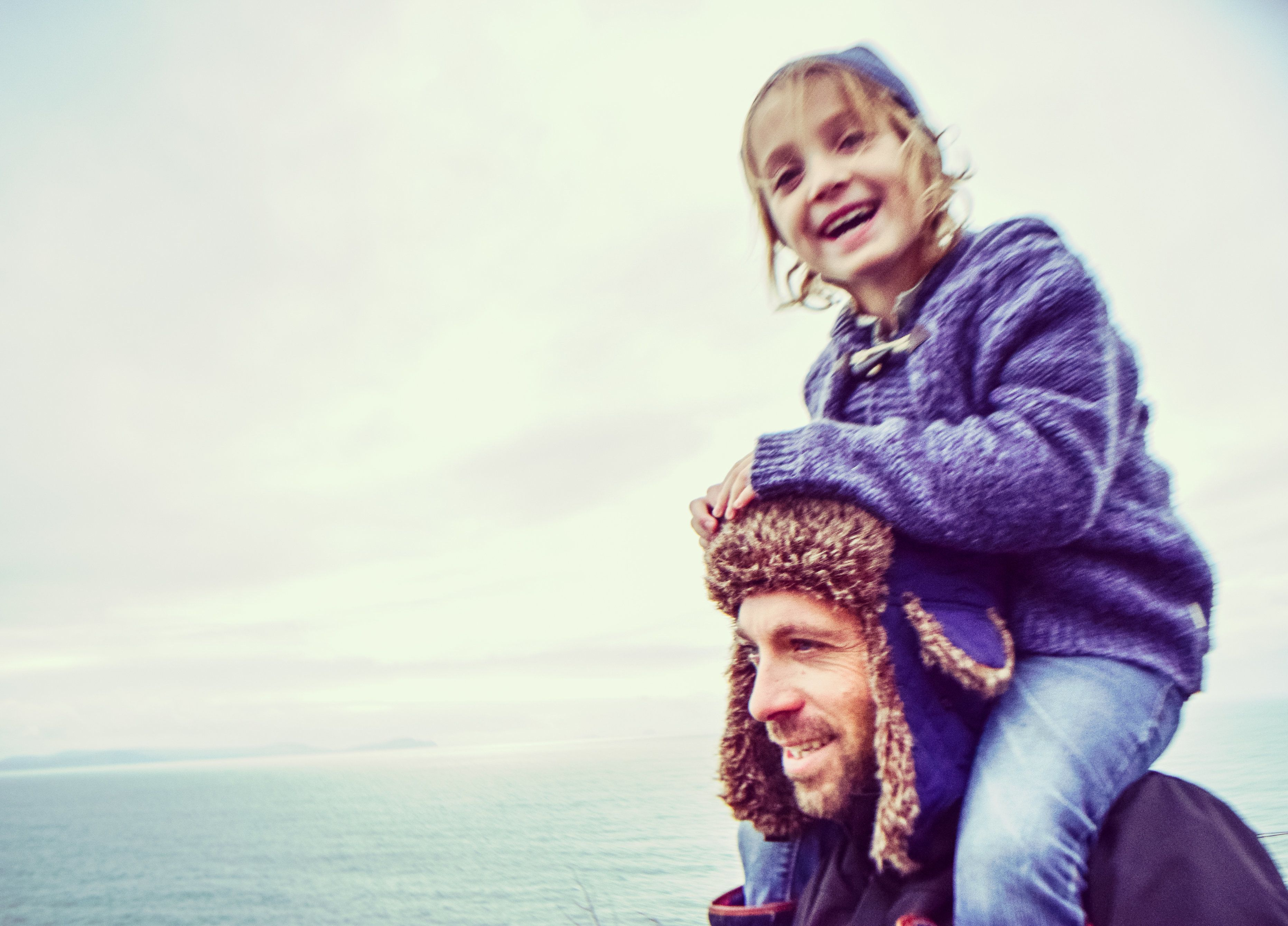 Little child catches a ride with dad, both are bundled for cold weather with an ocean backdrop