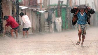 TUMAN, PERU:  A child shields himself from torrential rains with his jacket as he runs through a flooded dirt street while local residents(L) sweep mud and water out of their shacks in the town of Tuman, 820Km north of Lima, 17 March. Health authorities report that the flooding caused by the meteorological phenomenon 'El Nino' has exacerbated poor sanitary conditions in the poorest parts of Peru, provoking outbreaks of cholera, malaria, dysentery and conjunctivitis.  AFP PHOTO/Jaime RAZURI (Photo credit should read JAIME RAZURI/AFP/Getty Images)