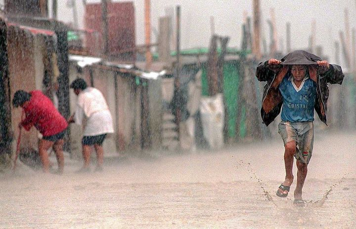 A child shields himself from the rain during an extreme El Niño event in Lima, Peru. Health authorities reported