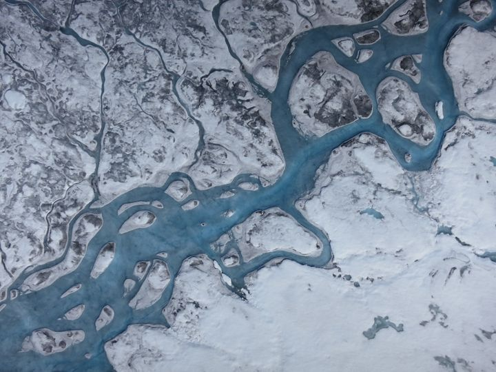 An aerial image of Greenland shows rivers of meltwater and areas of dark ice. Greenland's surface is absorbing more solar rad