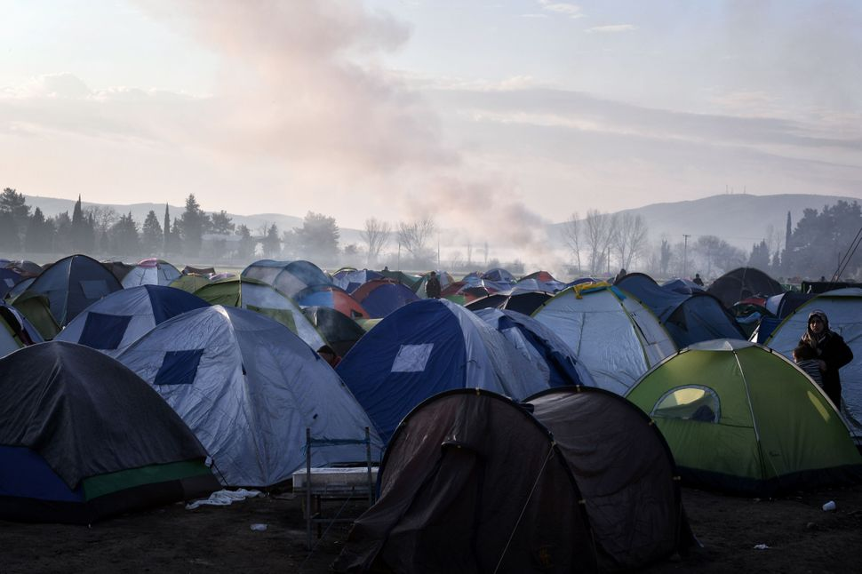 Smoke rises in the distance behind a woman standing among tents in the makeshift camp in Idomeni. Since the border crossings