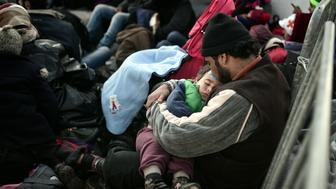 A man holds a child as refugees and migrants wait to cross the Greek-Macedonian border near the Greek village of Idomeni on March 3, 2016. Macedonia on March 2 allowed around 250 migrants to cross its border with Greece, as 10,000 more were left waiting in miserable conditions, Greek officials said. / AFP / LOUISA GOULIAMAKI        (Photo credit should read LOUISA GOULIAMAKI/AFP/Getty Images)