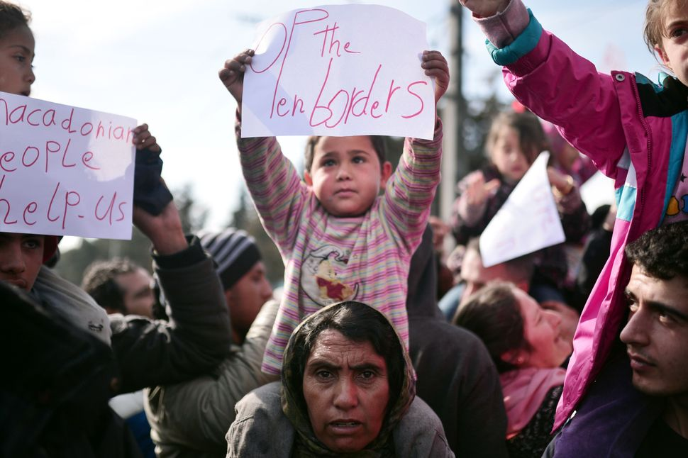 """A child sits on a woman's shoulders and holds a sign that reads """"Open the borders"""" at the makeshift camp in Idomeni. Migrants"""