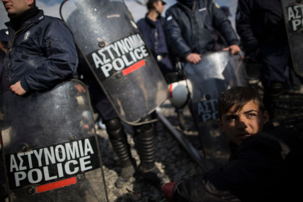 A young boy sits in front of police officers as a train attempts to pass in Idomeni.