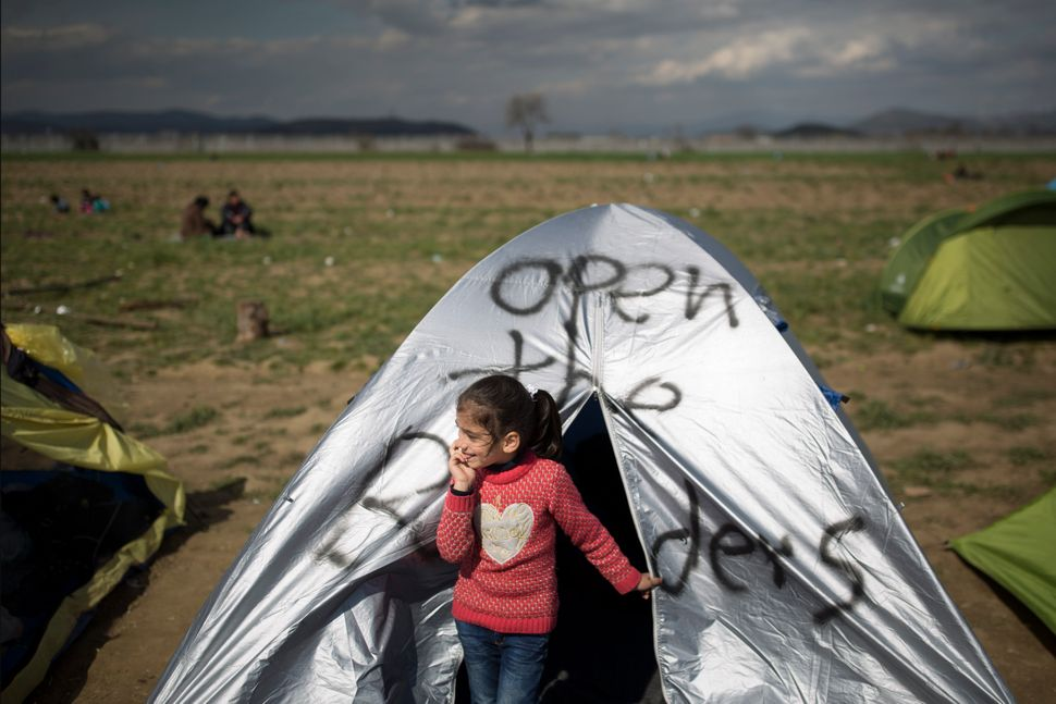 Thousands of children are among the migrants and refugees stuck at the border.This young girl stands outside her tent o