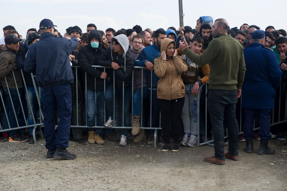 A crowd of migrants waits behind a gate in Idomeni, Greece, to cross the border into Macedonia on March 2, 2016.