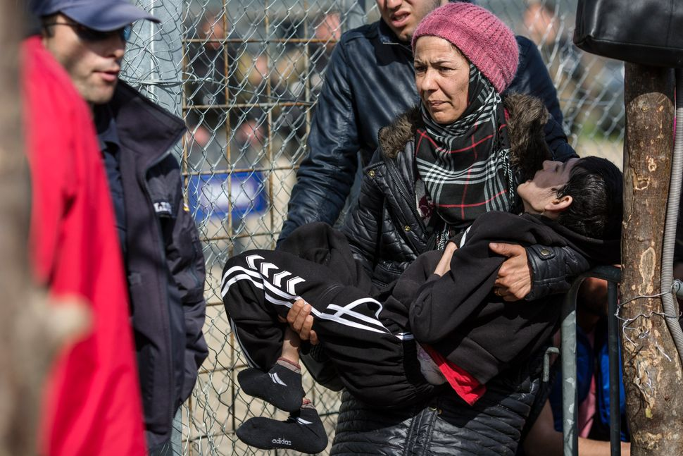 A woman holding a disabled child waits to cross the Greece-Macedonia border on March 3, 2016. Authorities are only allowing a
