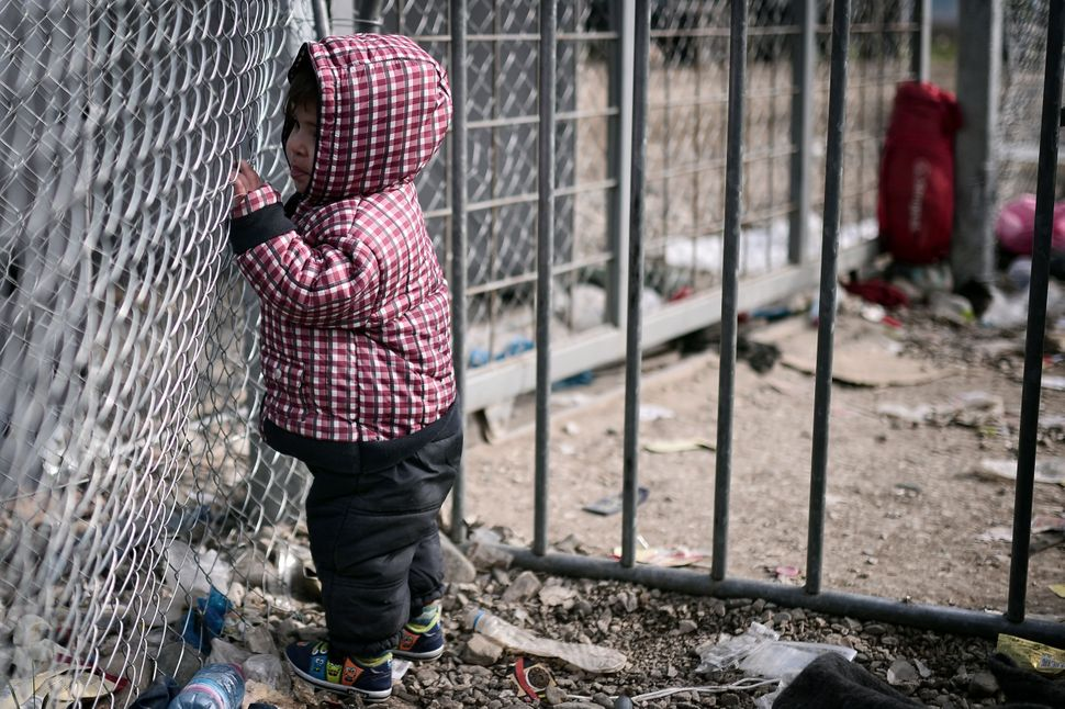 A child stands at a gate on the Greek-Macedonian border on March 3, 2016.
