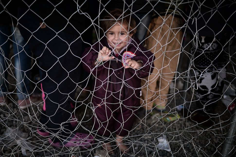 A migrant child waits to get milk at the overcrowded makeshift camp in Idomeni.The bottleneck in crossing the border&nb