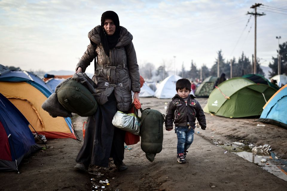 A woman walks with a child as she arrives to a makeshift camp at the Greek-Macedonian border near the Greek village of Idomen