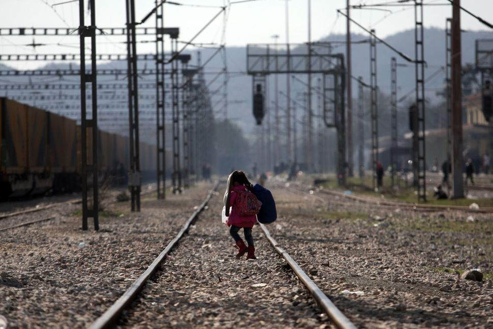 A child walks on a train track as migrants and refugees wait to cross the Greek-Macedonian border. EU President Donald Tusk o