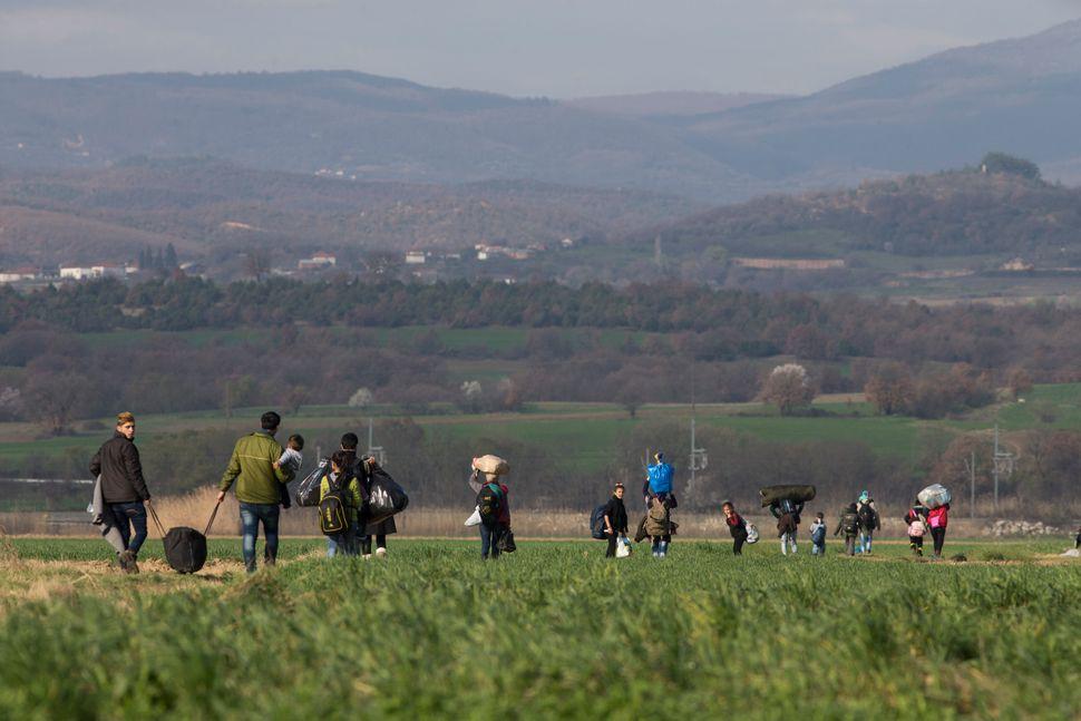 Refugee families walk through fields under mountains towards the Greek-Macedonian border.