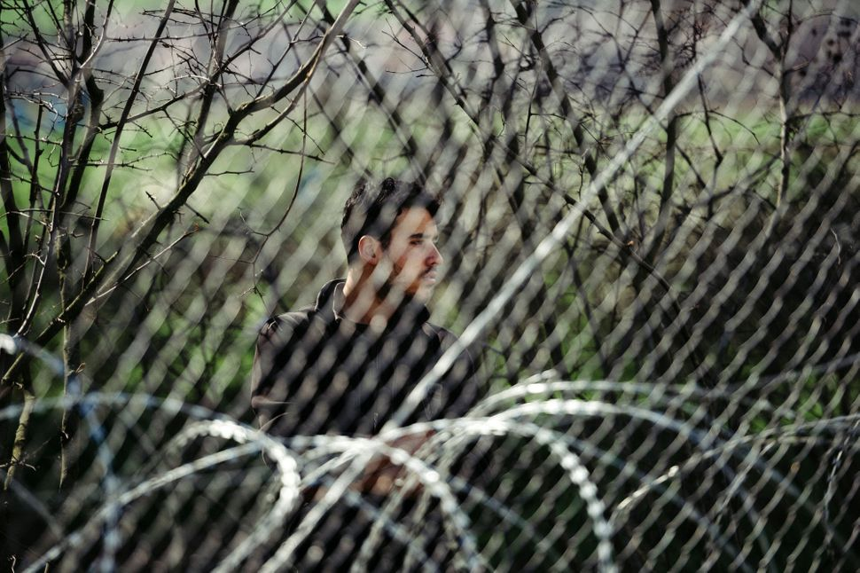 A man stands behind a fence near the Greece-Macedonia border. Some 30,000 migrants and refugees are currently stranded in Gre