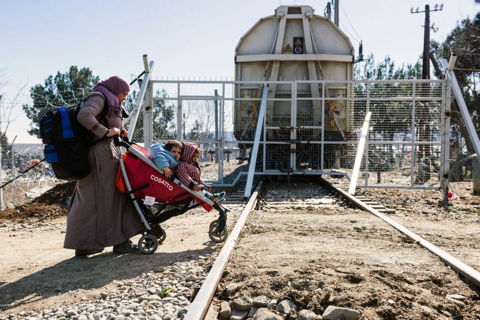 A woman pushes her children in a stroller after they cross the border between Greece and Macedonia.Since Balkan nations