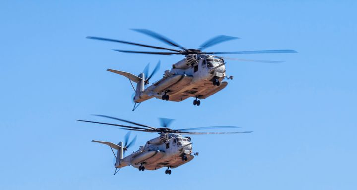 Two Marine Corps CH-53E Super Stallion helicopters fly in formation.