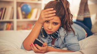 Teenage girl lying on bed in her room and checking smart phone. She is disappointed with content on her mobile phone. Resting after studying. Evening or night with beautiful yellow lights lightning the scenes.
