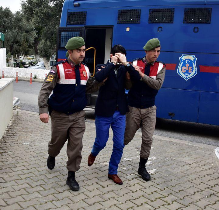 Turkish gendarmeries escort aSyrian arrested on suspicion of causing the deaths of 5 refugees, including Aylan Kurdi.