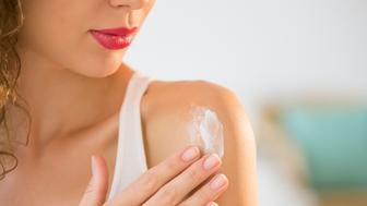 USA, New Jersey, Young woman applying cream on shoulder