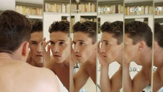 Man touching eyebrow, focus on multiple reflections in mirrors
