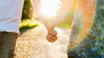 Midsection of couple holding hands on dirt road against bright sun