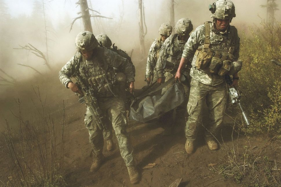 U.S. soldiers carry the body of a fallen comrade after a Taliban assault in the Korengal Valley.