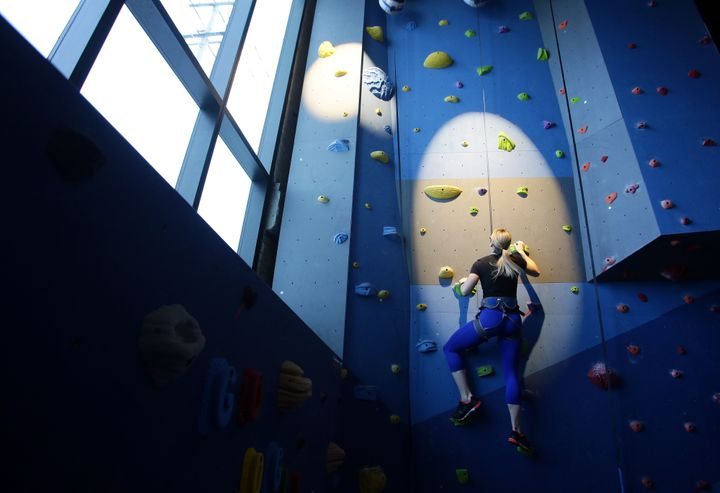 An employee climbs the rock wall in the fitness center at Google Canada's engineering headquarters in Waterloo, Ontario, Cana