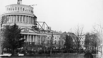 View of the United States Capitol Building, showing the dome under construction, on Pennsylvania Avenue, Washington DC, USA, pictured on the day of the inauguration of President Abraham Lincoln, 4 March 1861. (Photo by Fotosearch/Getty Images).