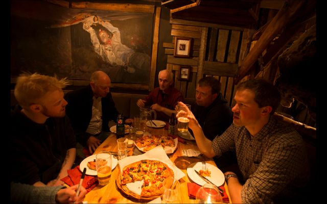 Sveinung Thesen (right, front) and choir members enjoy pizza and beer after the show.