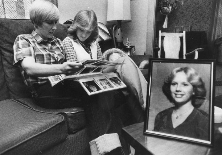 With a photo of Joyce McLain, who was murdered, in the foreground, mother Pamela McLain and sister Wendy leaf though the fami