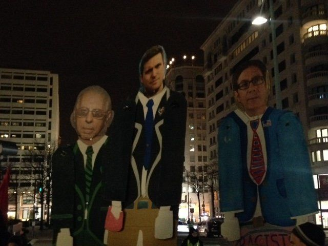 Protesters outside the white nationalist conference held puppets of the conference's three speakers (from left to right): Kev