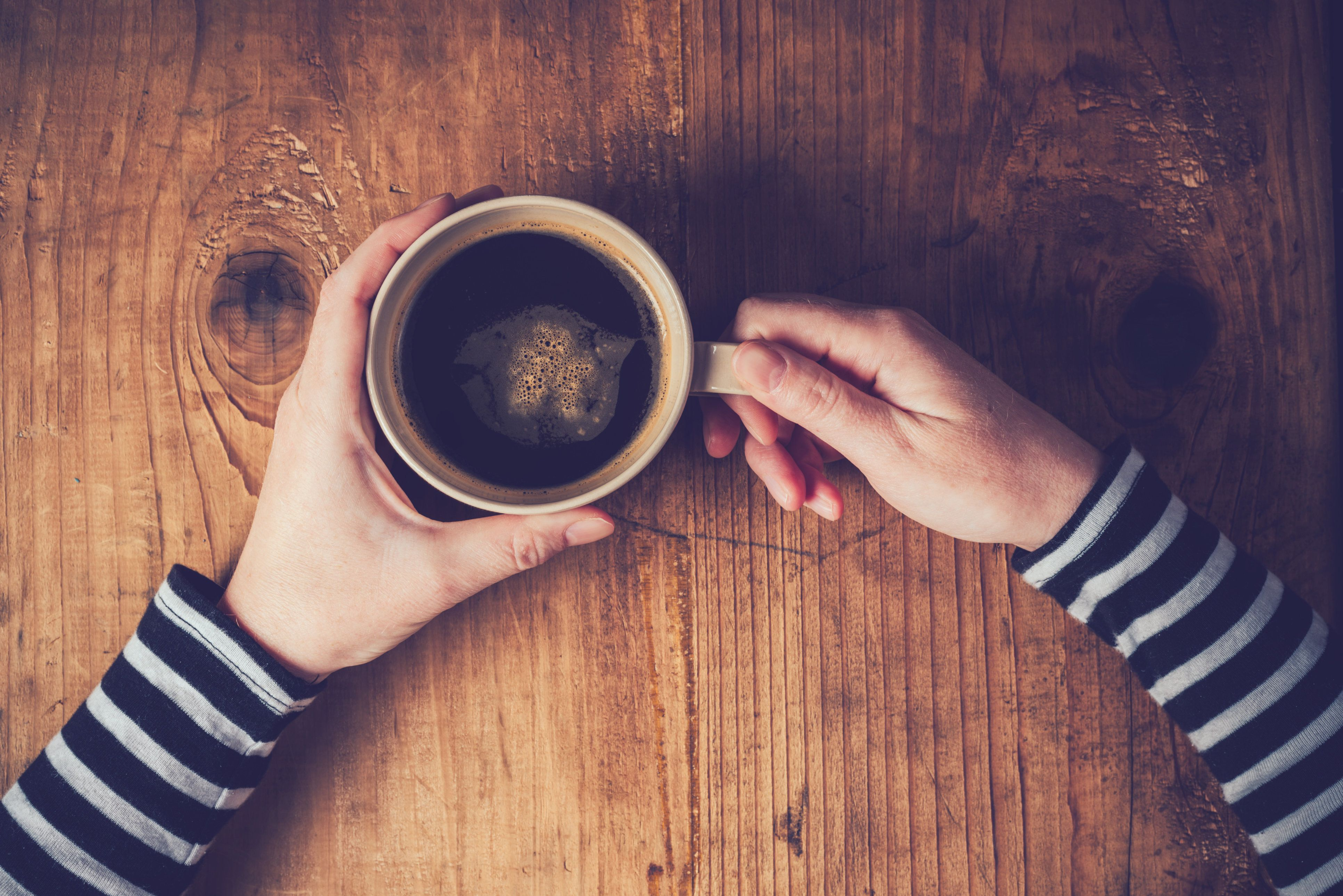 Lonely woman drinking coffee in the morning, top view of female hands holding cup of hot beverage on wooden desk, retro toned.