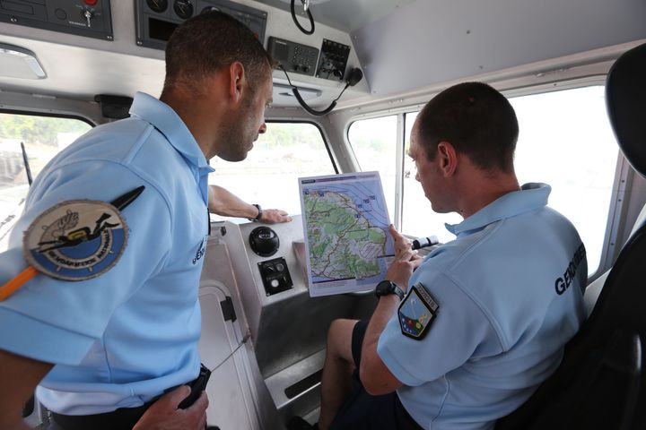 French maritime gendarmes look at a map of the search for MH370 wreckage on the French island of Réunion las
