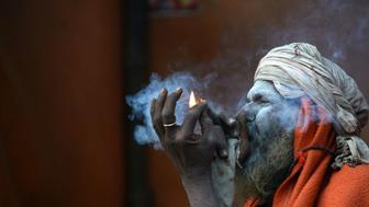 A Nepalese Sadhu (Hindu holy man) smokes a chillum, a traditional clay pipe, as a holy offering to Lord Shiva, the Hindu god of creation and destruction, near the Pashupatinath Temple in Kathmandu on March 6, 2016, on the eve of the Hindu festival Maha Shivaratri.  Hindus mark the Maha Shivratri festival by offering special prayers and fasting.  / AFP / PRAKASH MATHEMA        (Photo credit should read PRAKASH MATHEMA/AFP/Getty Images)
