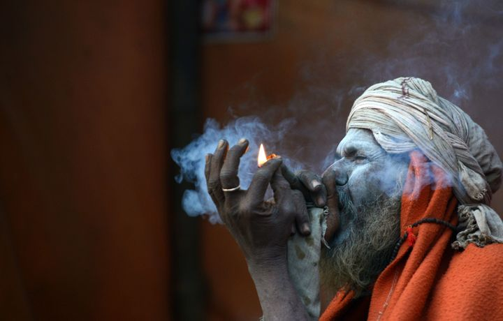 A Nepalese Sadhu (Hindu holy man) smokes a chillum, a traditional clay pipe, as a holy offering to Lord Shiva, the Hindu god