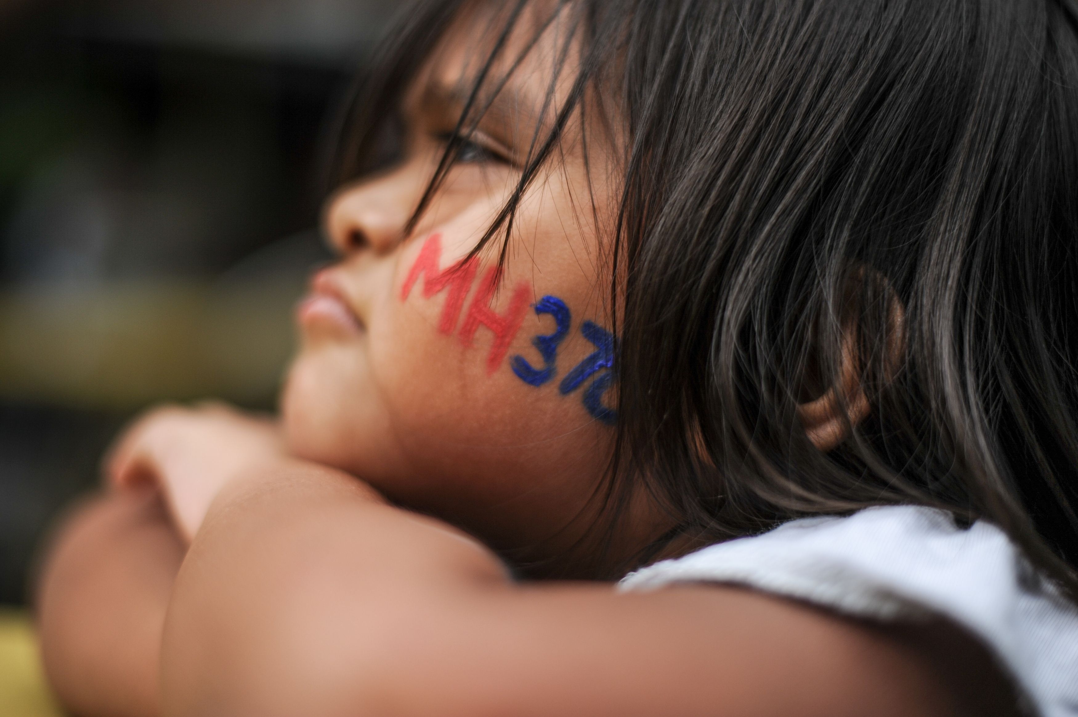 A boy with his face painted with the missing Malaysia Airlines ill-fated flight MH370 logo looks on during a memorial event in Kuala Lumpur on March 6, 2016.   Families of those lost on MH370 are preparing mark the upcoming second anniversary of when the Malaysia Airlines flight disappeared on March 8, 2014.  / AFP / MOHD RASFAN        (Photo credit should read MOHD RASFAN/AFP/Getty Images)