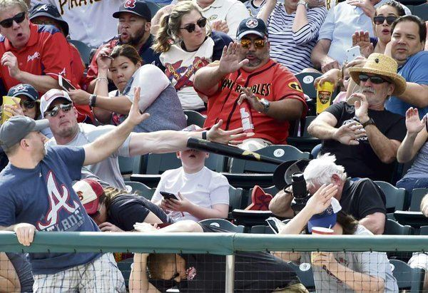 A father saves his son from a flying baseball bat during an MLB spring training game.