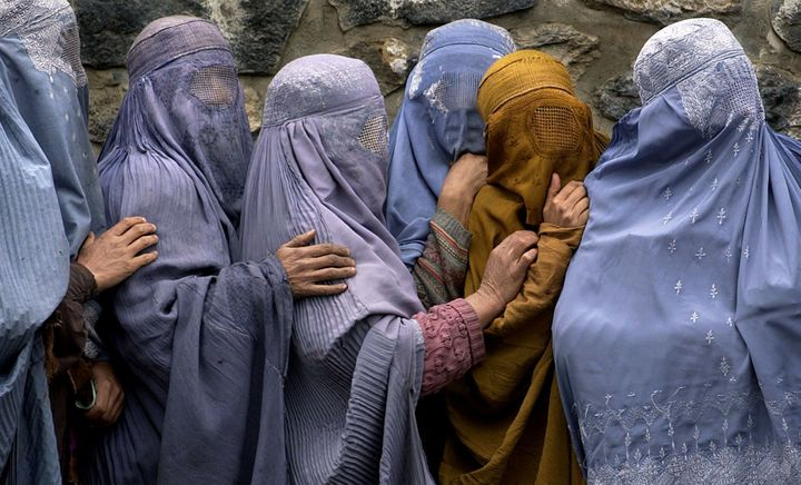 Women waiting in line to receive food in the Afghan capital, Kabul, remain as covered up as when the Islamic fundamentalist T