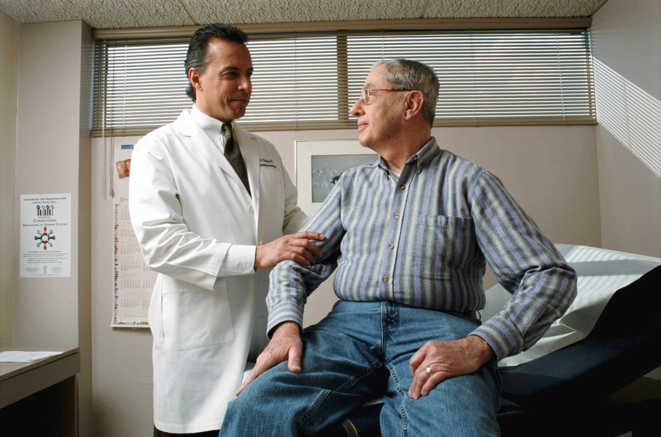 Male doctor looking at male patient in office