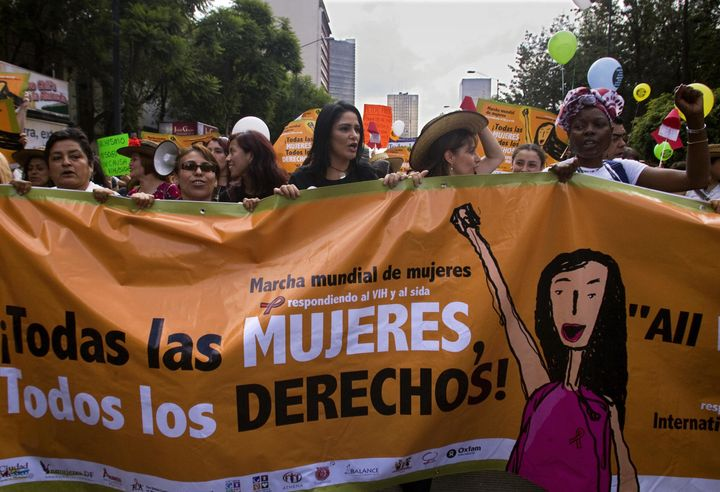 A group of women hold a banner during the Women's World March at the Zócalo square in Mexico City on Aug. 5, 2008, on