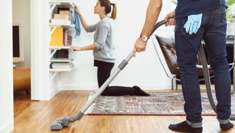 Low section of man vacuuming floor while woman cleaning shelves in background at home