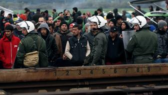 People wait as a cargo train passes by on March 9, 2016, at the Greek-Macedonian border, near the Greek village of Idomeni, where thousands of refugees and migrants are stranded by a Balkan border blockade. The main migrant trail from Greece to northern Europe was blocked March 9 after western Balkan nations slammed shut their borders, hiking pressure for an EU-Turkey deal and exacerbating a dire situation on the Macedonian border. More than 14,000 mainly Syrian and Iraqi refugees are camping out by the northern Idomeni border crossing with Macedonia -- many of them for weeks -- at a muddy, unhygienic camp operated by beleaguered aid groups.   / AFP / SAKIS MITROLIDIS        (Photo credit should read SAKIS MITROLIDIS/AFP/Getty Images)