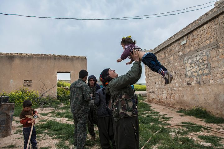 Sarah, a member of YPJ, spends some time with a little girl of a family she is visiting on her way from one village to anothe