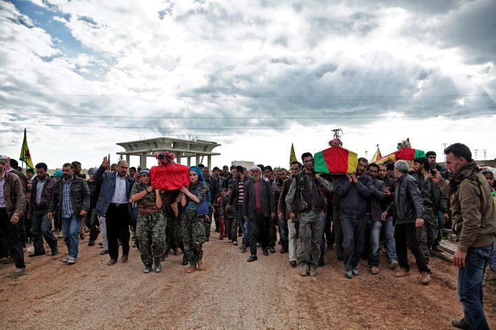 On April 14, 2015, a group of YPJ and YPG (People's Protection Unit) fighters carry the coffins of Kurdish fighters who