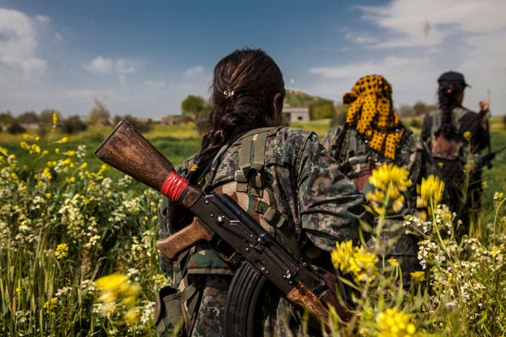 Three fighters from the YPJ (Women's Protection Units), walk through the flower fields in Western frontline near the city of