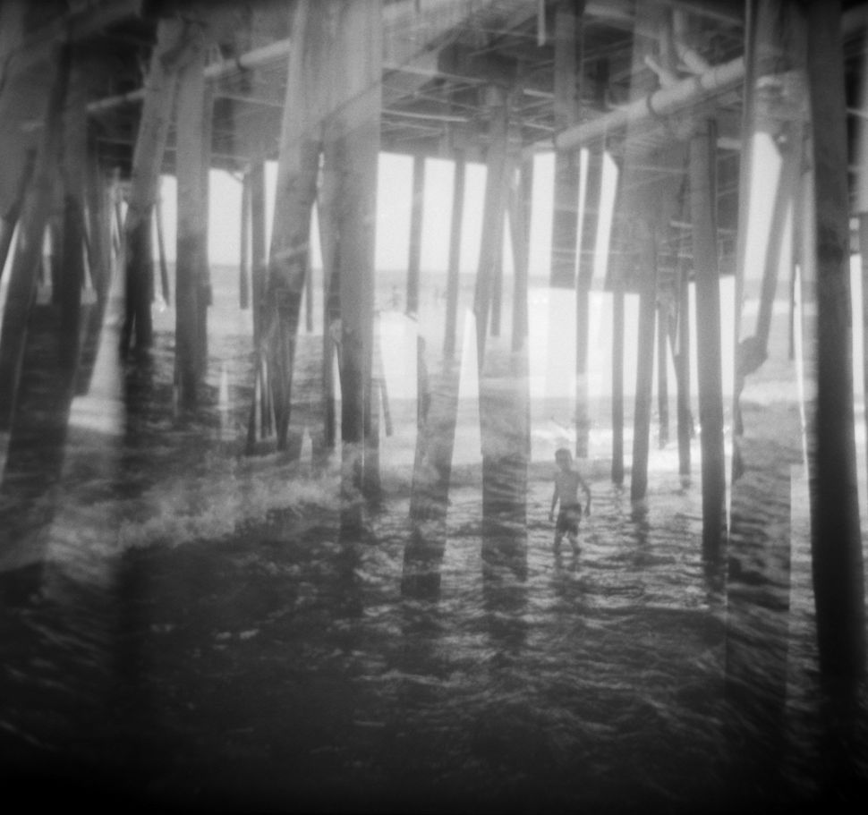 """Boy Under Piers, Old Orchard Beach, Maine, 2014."""