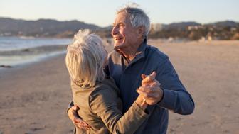 Senior Male and Female Couple Romantic Beach Lifestyle Dancing