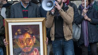 ROME, ITALY - 2016/02/25: A man holding a framed-picture of Giulio Regeni and beside him a man speaks using megaphone during protest in Rome. Sit-in in front of the Egyptian embassy in Rome to demand truth and justice for Julius Regeni, the young Italian researcher tortured and brutally murdered in Cairo, and to all those nameless young Egyptians who have suffered the same cruelty. (Photo by Patrizia Cortellessa/Pacific Press/LightRocket via Getty Images)