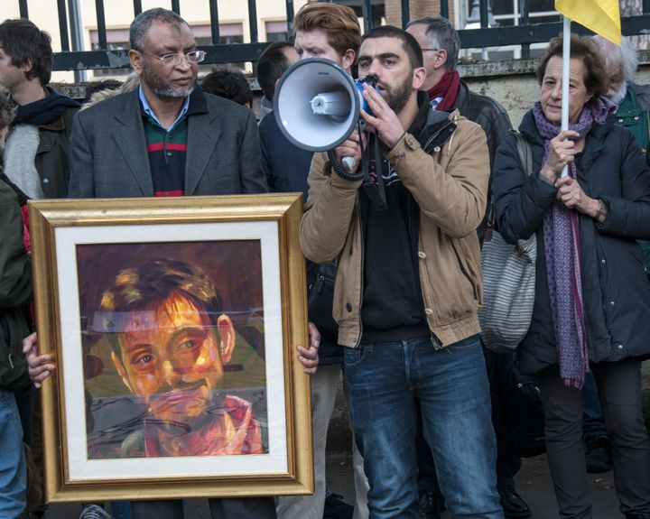 A man holdsa framed picture of Giulio Regeni and beside him a man speaks using a megaphone during a protest in front of