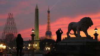 A man takes a picture of the Eiffel tower at sunset, near Place de la Concorde in Paris, on February 28, 2016. / AFP / LUDOVIC MARIN        (Photo credit should read LUDOVIC MARIN/AFP/Getty Images)