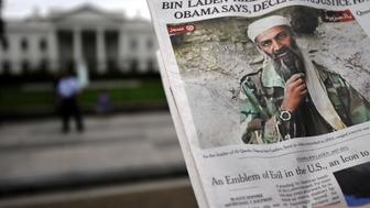 A man takes pictures of the front page of a newspaper featuring a picture of Al-Qaeda leader Osama bin Laden, in front of the White House in Washington, DC, on May 2, 2011. Al-Qaeda leader Osama bin Laden was shot dead deep inside Pakistan in a night-time helicopter raid by US covert forces, ending a decade-long manhunt for the mastermind of the September 11 attacks. 'Justice has been done,' President Barack Obama declared in a dramatic televised address late Sunday, sparking raucous celebrations across the United States, after an operation that officials said lasted less than 40 minutes. AFP Photo/Jewel Samad (Photo credit should read JEWEL SAMAD/AFP/Getty Images)